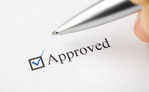 Checkbox labeled Approved with hand holding pen that have just finished checking the box